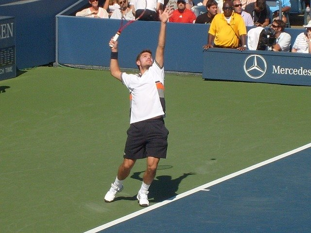A man hitting a ball with a racket on a court